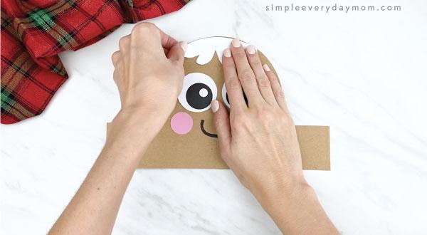 hands gluing icing hair onto gingerbread headband craft