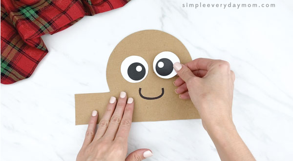 hands gluing eye onto gingerbread headband craft
