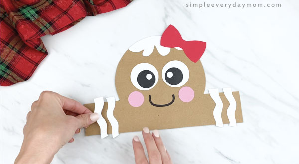 hands gluing icing accents onto gingerbread headband craft