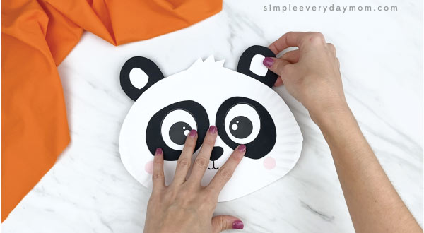 hands gluing ears to paper plate panda craft
