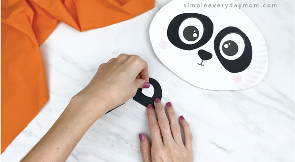 hands gluing inner ear to outer ear of paper plate panda craft
