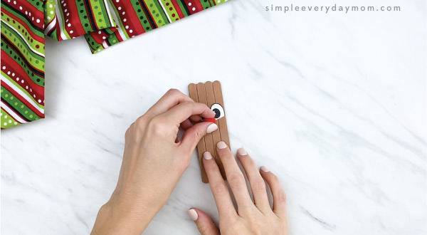 hands gluing red pom pom nose on popsicle stick reindeer