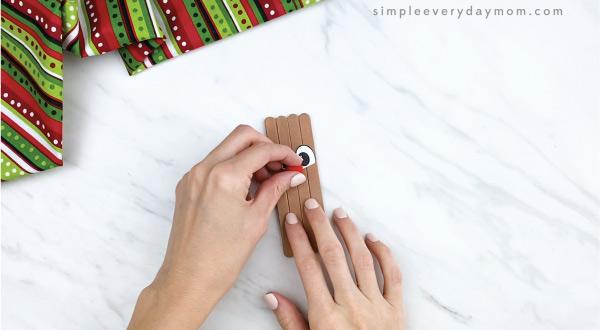 hands gluing red pom pom nose on popsicle stick reindeer
