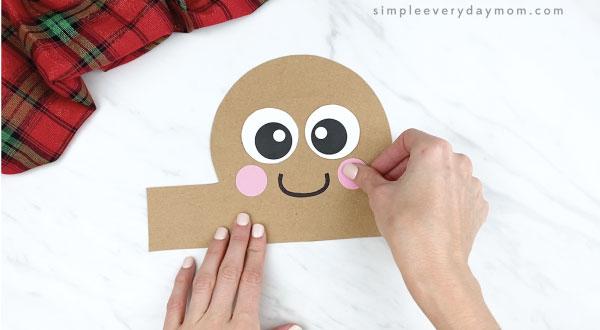hands gluing cheeks onto gingerbread headband craft