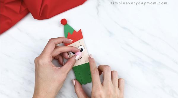 hands gluing pom pom nose onto popsicle stick elf craft