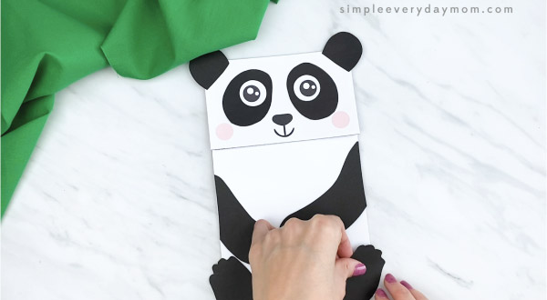 hands gluing feet to paper bag panda craft