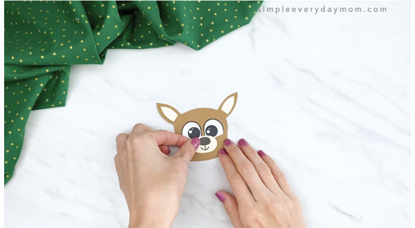 hands gluing nose to reindeer finger puppet craft