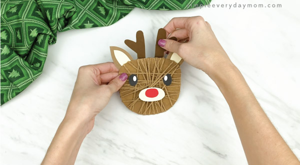hands gluing antlers to yarn wrapped reindeer craft