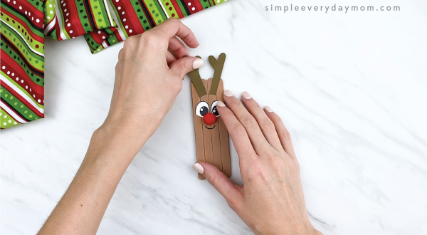 hands gluing antlers on popsicle stick reindeer