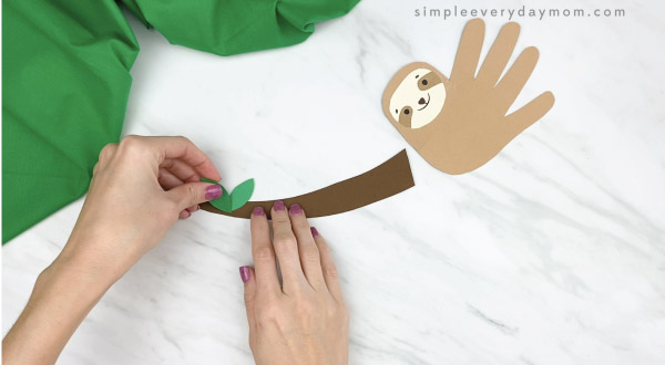 hands gluing paper leaves to paper branch