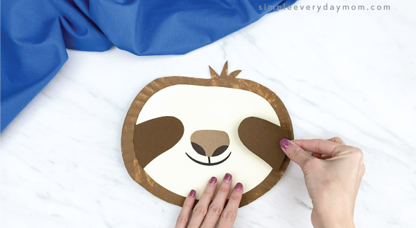 hands gluing eye area to paper plate sloth craft