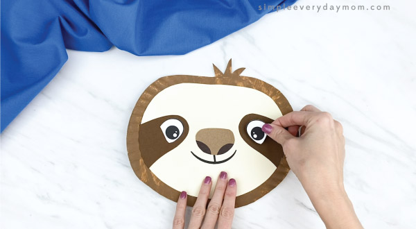 hands gluing eye to paper plate sloth craft