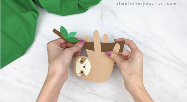 hands gluing handprint sloth onto paper branch
