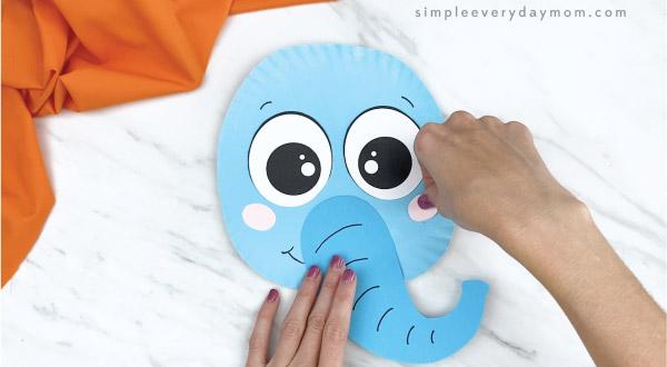 hands gluing cheeks onto paper plate elephant