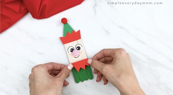 hands gluing elf shirt trim onto popsicle stick elf craft