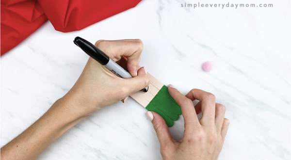 hands drawing smile onto popsicle stick elf craft