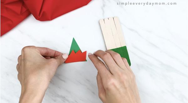 hands gluing elf hat trim onto popsicle stick hat