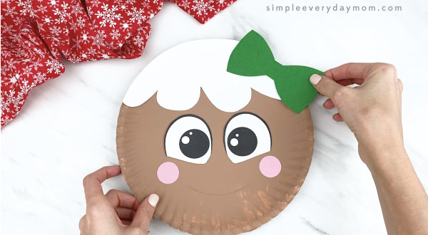 hands gluing bow to girl paper plate gingerbread craft
