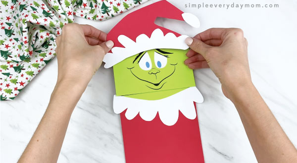 hands gluing Santa hat onto paper bag Grinch
