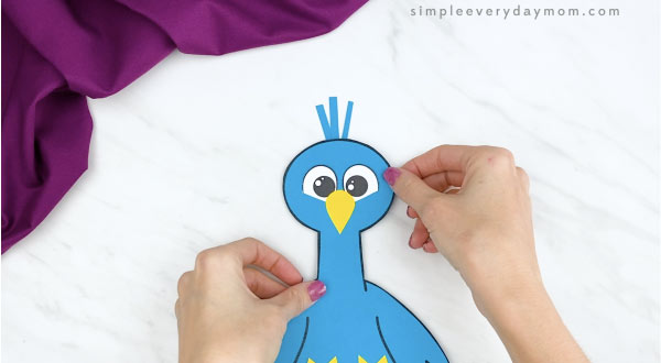 hands gluing head feathers on handprint peacock craft