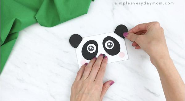 hands gluing ears to paper bag panda craft