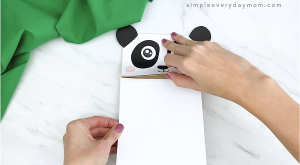 hands gluing white paper to paper bag panda craft