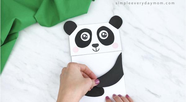 hands gluing arms to paper bag panda craft