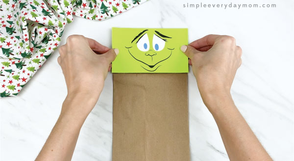 hands gluing face onto paper bag Grinch