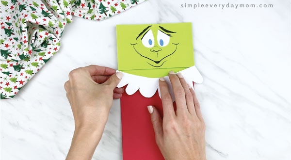hands gluing Santa suit trim onto paper bag Grinch