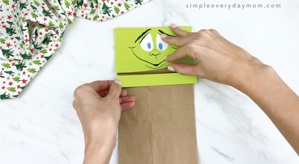 hands gluing neck onto paper bag Grinch