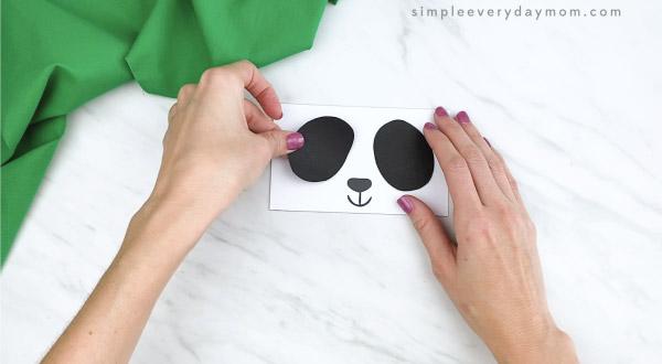 hands gluing eye area to paper bag panda craft