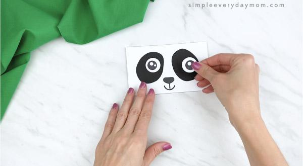 hands gluing eyes to paper bag panda craft