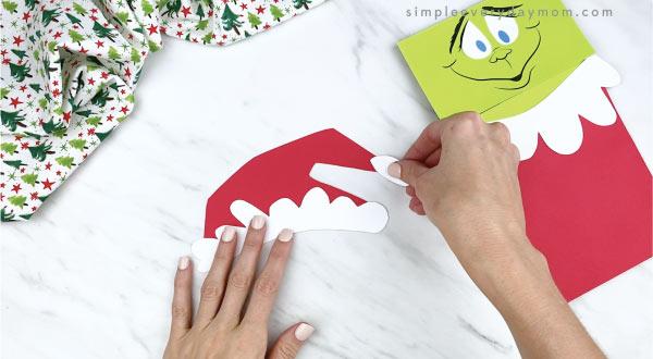 hands gluing Santa hat pom