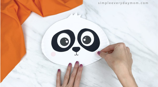 hands gluing cheeks to paper plate panda craft
