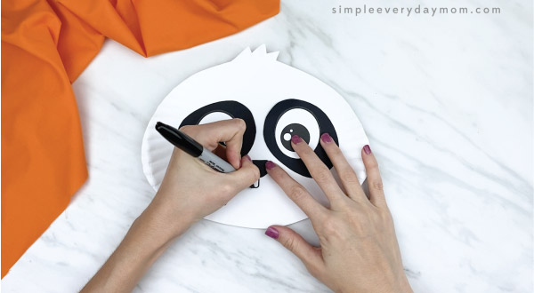 hands drawing mouth onto paper plate panda craft