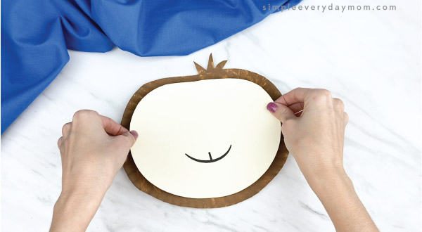 hands gluing face to paper plate sloth craft