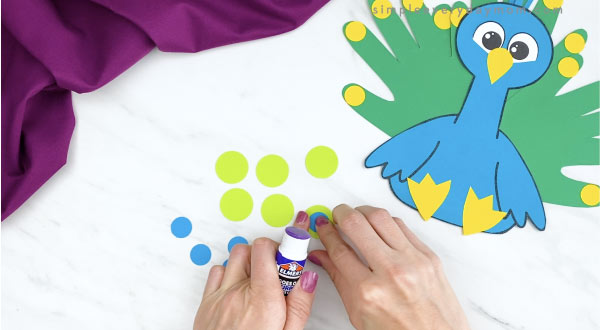 hands gluing blue circles to bigger green circles