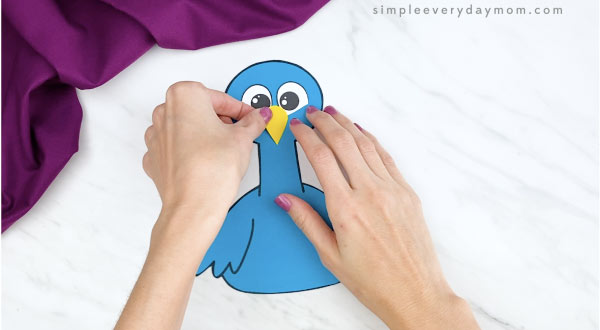 hands gluing nose on handprint peacock craft
