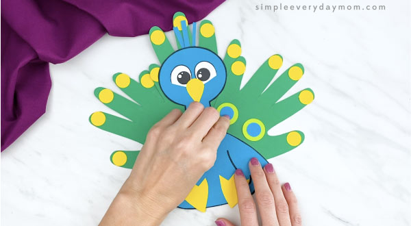 hands adding feather details to handprint peacock craft