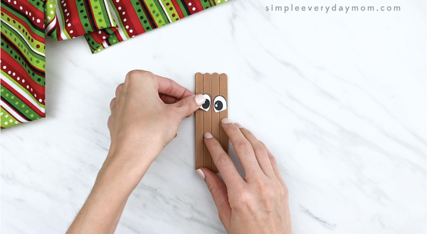 hands gluing eyes on popsicle stick reindeer