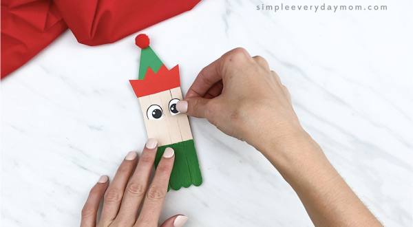 hands gluing eyes onto popsicle stick craft
