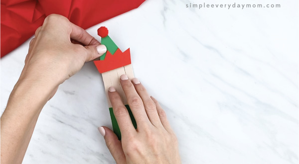 hands gluing hat onto popsicle stick craft