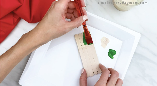 hands gluing popsicle sticks green