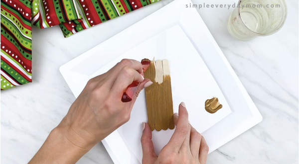 hands painting 4 popsicle stick brown