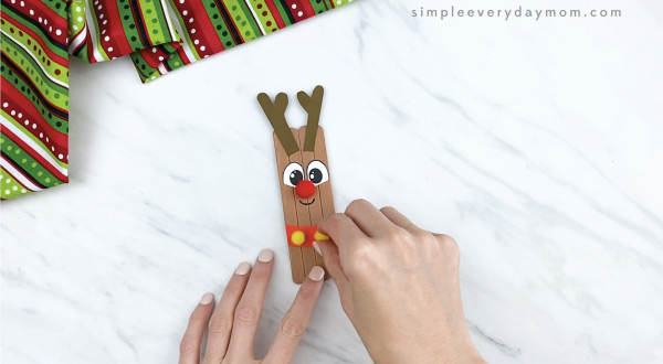hands gluing yellow pom poms on popsicle stick reindeer
