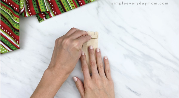 hands gluing 4 popsicle sticks together