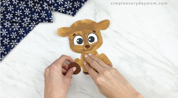 hands gluing hooves onto printable reindeer craft