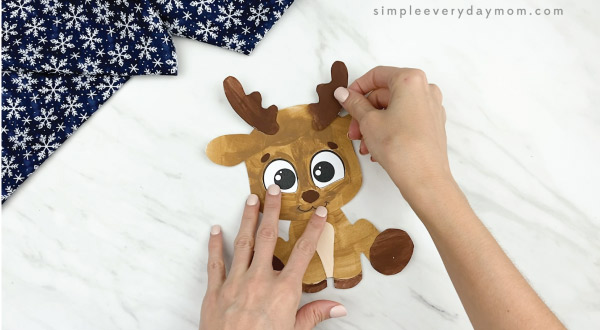 hands gluing antlers to printable reindeer craft