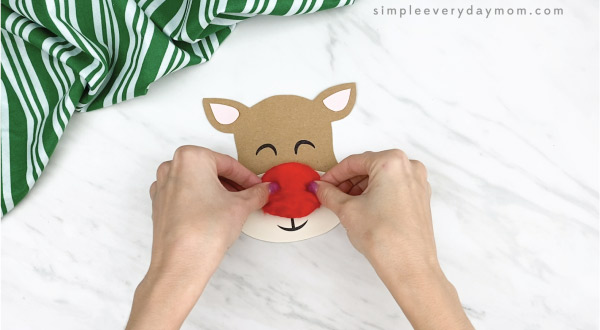 hands gluing pom pom nose to clothespin reindeer craft