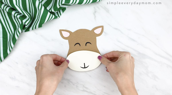 hands gluing nose to clothespin reindeer craft